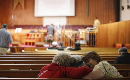 Three women console each other before a memorial service for Oikos University at Allen Temple Baptist Church in Oakland on Tuesday